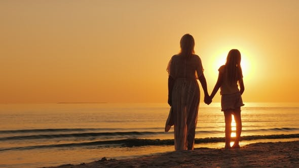 Thumbnail for A Woman Holds a Child's Hand, Stand Together on the Seashore, Look at a Beautiful Sunset. Mother