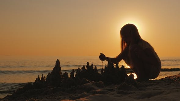 Thumbnail for Silhouette of a Child, Builds a Sand Castle on the Beach, a Beautiful Sunset