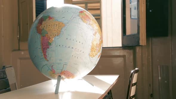 Thumbnail for World Globe Map in a Classroom With Dust Particles.
