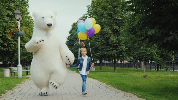 Thumbnail for Happy Childhood with Your Favorite Toys, a Big White Bear Is Having Fun with a Child of 7 Years Old