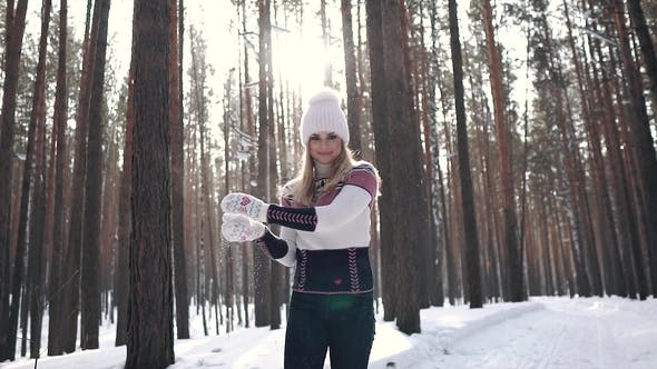 Thumbnail for Girl Throws a Snowball at the Camera and Smiles. Portrait of a Cute and Carefree Girl in a Sweater