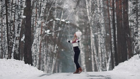 Thumbnail for Young Smiling Girl Is Happily Spinning in the Winter Forest