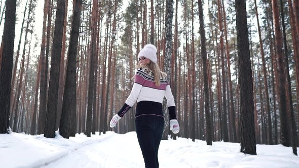 Thumbnail for Girl in a Sweater and Hat on a Walk in the Winter Forest