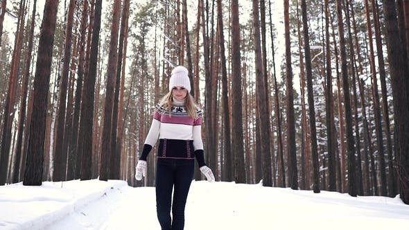Thumbnail for Cheerful Girl Walking Through the Winter Forest and Smiling. Portrait of a Young Woman in a Sweater