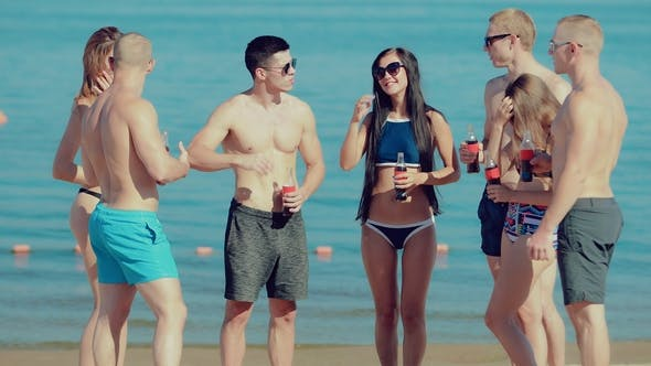 Young Happy Friends Stand in a Semicircle and Communicate on the Beach Near the Water with Soda