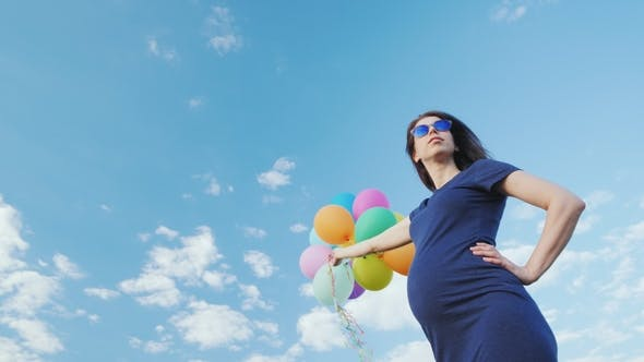 Thumbnail for Happy Pregnant Woman Playing with Balloons Against the Blue Sky