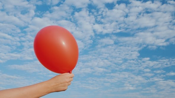 Thumbnail for Air Comes From the Red Air Balloon and It Becomes Limp. Against the Background of the Blue Sky