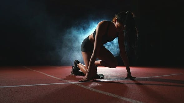 Thumbnail for Young Woman Athlete in Black Shorts and a T-shirt Is Preparing To Start in the Race for 100 Meters