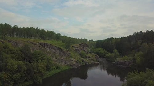 Drone View. Sniper Woman with a Sniper Rifle Sits on the Rocks on the River. Cameta Moving To Object