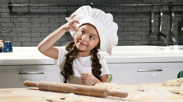 Thumbnail for Little Cute Girl Pretending Chef in Cook Hat in Kitchen Rolling Dough with a Rolling Pin Making