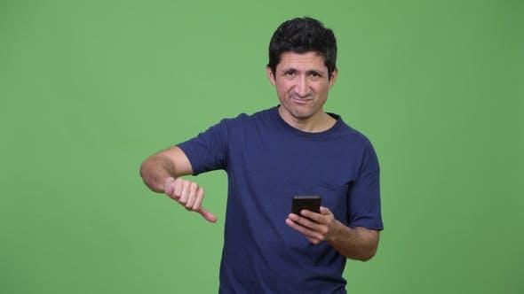 Hispanic Man Using Phone and Giving Thumbs Down