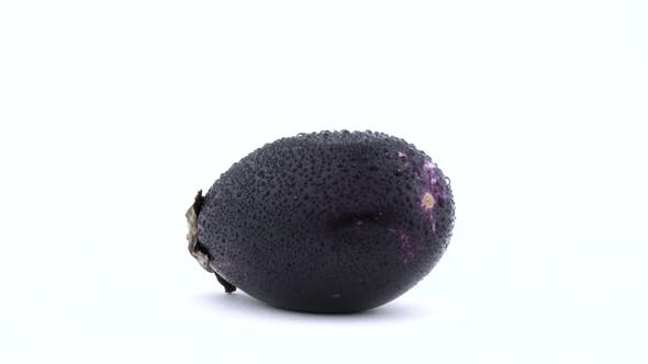 Cover Image for One Whole Purple Mini Eggplant with Water Drops. Rotating on the Turntable. Isolated on the White