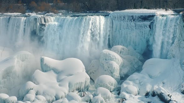 Thumbnail for Magnificent View of the Frozen Niagara Falls. Water Flows Among the Rocks Covered with Ice and Snow