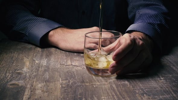 Thumbnail for Man Holding a Glass of Ice and Pour Whiskey