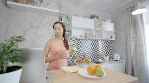 Thumbnail for Beautiful Asian Woman Eating Apple While Checking Networks on Her Laptop in the Kitchen