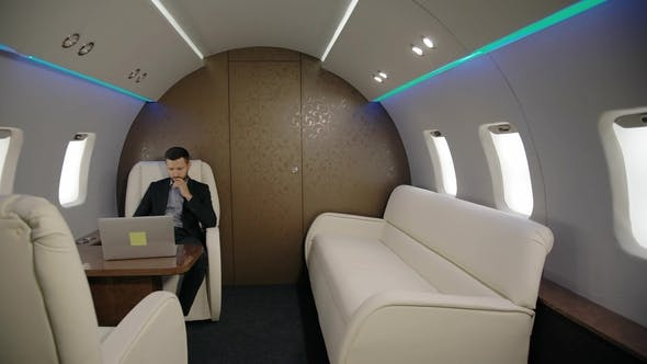 Thumbnail for Young Confident Lawyer Businessman Is Working with Laptop Sitting in Entrepreneur Airplane Interior