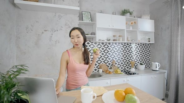 Thumbnail for Attractive Young Woman Is Using Laptop, Eating Apple in Modern Kitchen