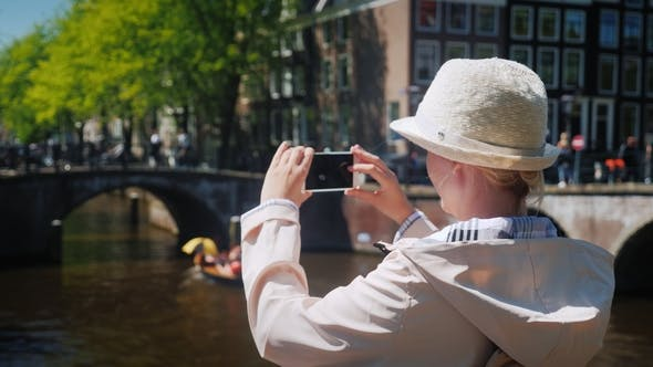 Thumbnail for An Active Traveler Woman Takes Pictures of a Beautiful View of the Canal in Amsterdam