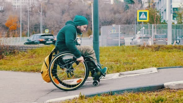 Disabled Man in Wheelchair Makes Attempt To Steer His Wheelchair Over a Ramp on the Street