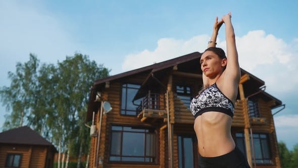 Thumbnail for Woman on the Grass Doing Yoga on the Background of a Beautiful House. The Concept of a Healthy