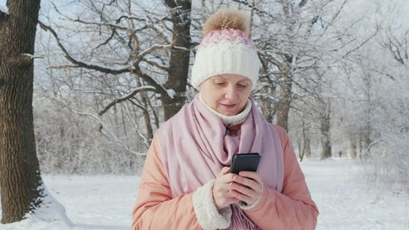 Thumbnail for A Woman in a Pink Jacket Enjoys a Walk in a Winter Park. Uses a Mobile Phone