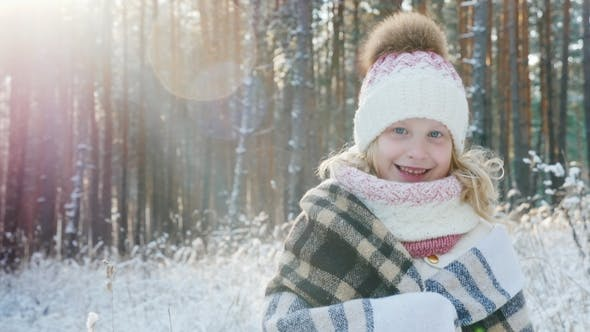 Thumbnail for Portrait of a Happy Little Girl Wrapped in a Plaid in a Snow-covered Winter Forest