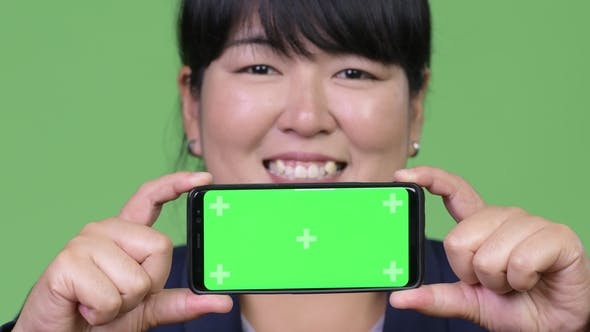 Thumbnail for Happy Overweight Asian Businesswoman Showing Phone