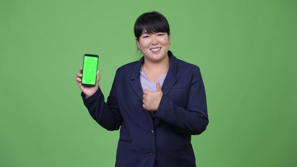 Cover Image for Happy Overweight Asian Businesswoman Showing Phone and Giving Thumbs Up