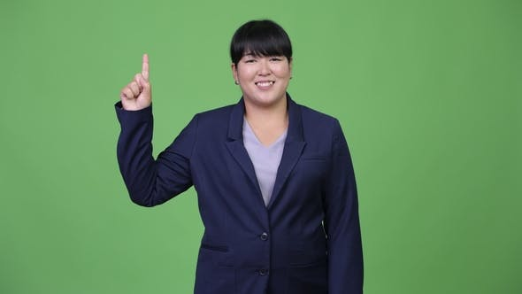 Thumbnail for Happy Overweight Asian Businesswoman Pointing Up