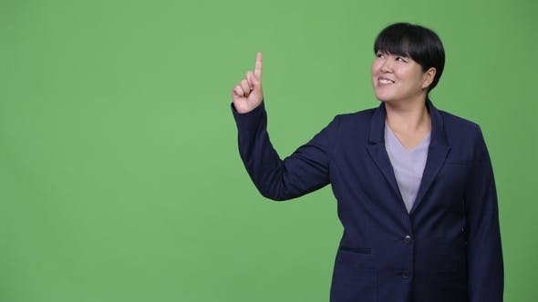 Thumbnail for Happy Overweight Asian Businesswoman Thinking While Pointing Up