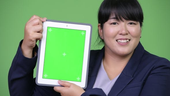 Thumbnail for Happy Overweight Asian Businesswoman Showing Digital Tablet