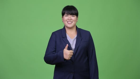 Thumbnail for Happy Overweight Asian Businesswoman Giving Thumbs Up