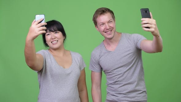 Thumbnail for Young Happy Multi-ethnic Couple Taking Selfie