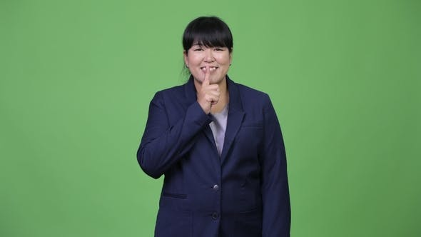 Thumbnail for Happy Overweight Asian Businesswoman with Finger on Lips