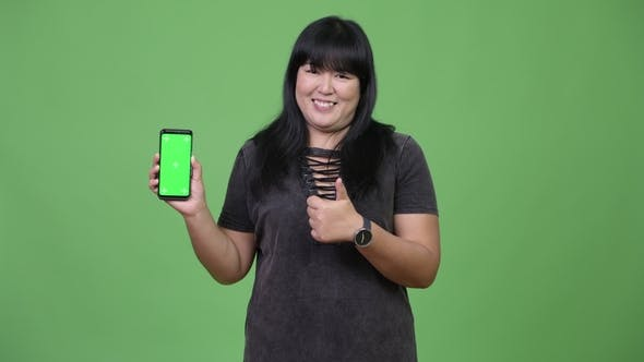 Thumbnail for Happy Overweight Asian Woman Showing Phone and Giving Thumbs Up