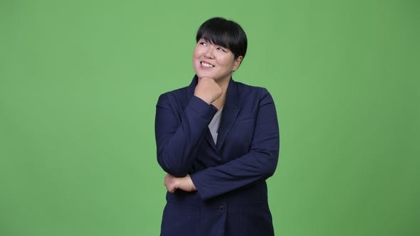 Thumbnail for Beautiful Overweight Asian Businesswoman Smiling While Thinking