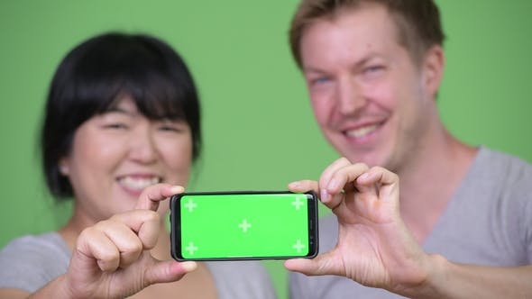 Thumbnail for Young Happy Multi-ethnic Couple Showing Phone Together