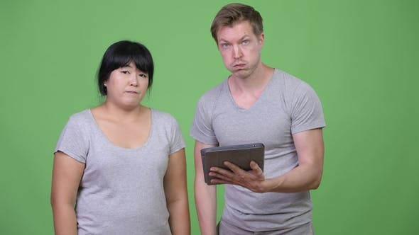 Thumbnail for Young Multi-ethnic Couple Using Digital Tablet and Getting Bad News Together
