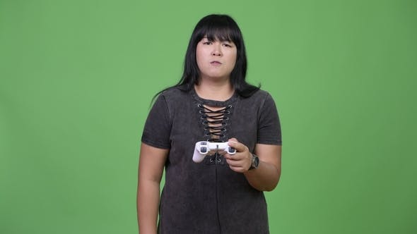 Thumbnail for Beautiful Overweight Asian Woman Playing Games and Losing