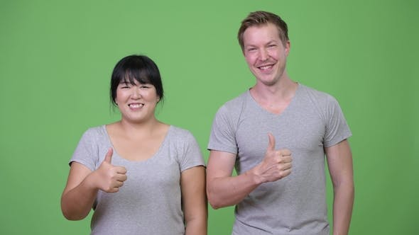Cover Image for Young Multi-ethnic Couple Giving Thumbs Up Together