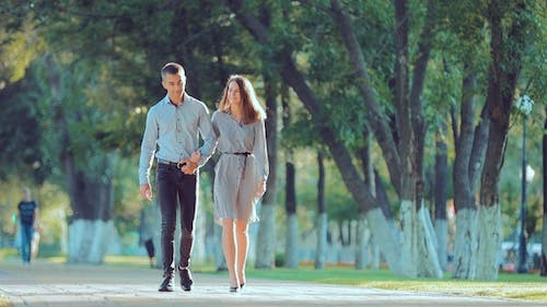 Young Couple Walking Along the City Park Together, Go To the Camera