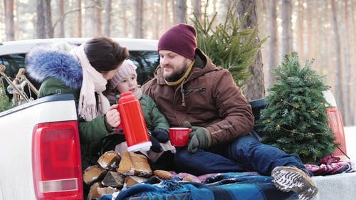 A Young Family of Three People Is Drinking Hot Tea From a Thermos, Sitting in the Back of a Car Near