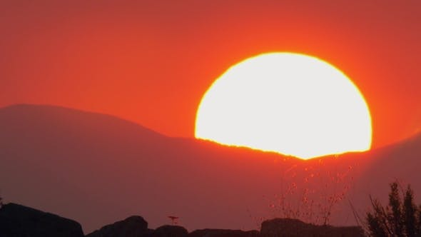 Thumbnail for Red Sky Scene with Sun Hiding Behind the Mountains