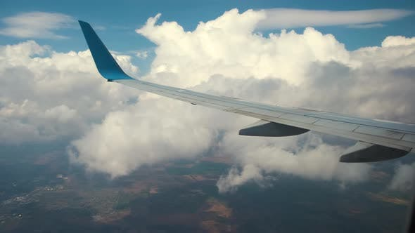 View of jet airplane wing from inside flying through white puffy clouds in blue sky.