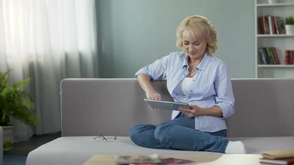 Thumbnail for Happy Middle-Aged Woman Viewing Funny Videos on Tablet, Sitting on Couch at Home