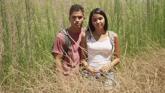 Serious Hispanic couple standing in shrubs