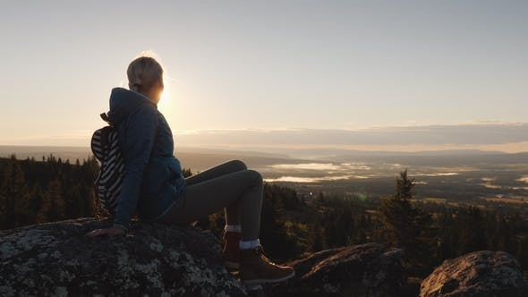 Thumbnail for A Woman Sits on a Rock Atop a Mountain