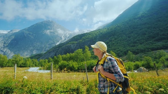 Thumbnail for An Active Woman with a Backpack Walks Against the Backdrop of the Mountains and the Briksdal Glacier