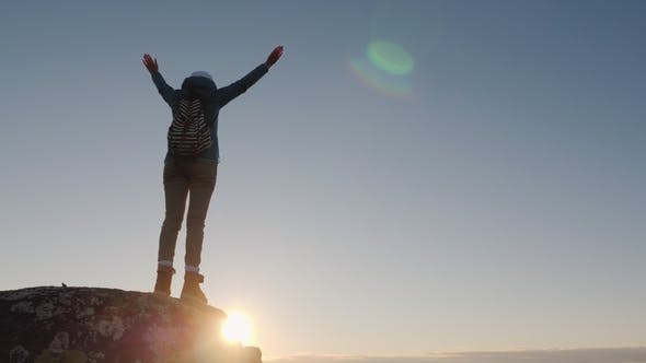 Thumbnail for A Successful Woman Traveler at the Top of the Mountain Raises Her Hands Up