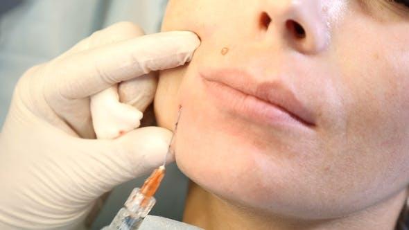 Thumbnail for von Frau im Schönheitszentrum und Kosmetikerin mit Spritze in den Händen. Arzt machen Anti-Aging-Injektionen